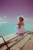 Caucasian woman takes rest at wooden pier to Indian ocean Royalty Free Stock Images