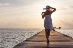 Caucasian woman takes rest at wooden pier to Indian ocean Royalty Free Stock Photo