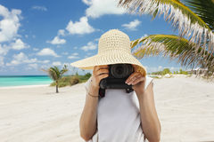 Caucasian woman taking pics on the beach. Royalty Free Stock Image