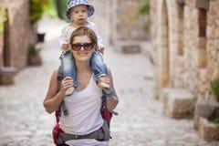 Caucasian woman tourist carrying her little son Stock Photos