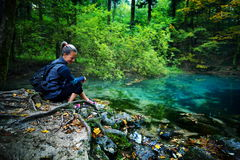 Caucasian woman tourist relaxing by the river, in the forest, Oc Royalty Free Stock Photos