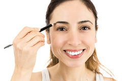 Caucasian woman using eyebrow pencil Stock Photography