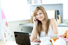 Caucasian woman using a laptop and a phone. In the kitchen at home Stock Photography