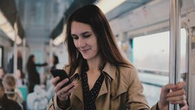 Caucasian woman using smartphone in subway car. Beautiful happy young office worker reading news from mobile app. 5G. 4K