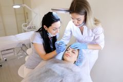 Caucasian woman visiting professional dermatologist and cosmetologist for permanent makeup. Caucasian girl visiting professional cosmetologist and dermatologist royalty free stock image