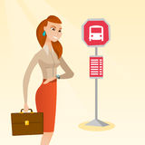 Caucasian woman waiting for a bus at the bus stop. Royalty Free Stock Photography