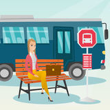 Caucasian woman waiting for a bus at the bus stop. Stock Image