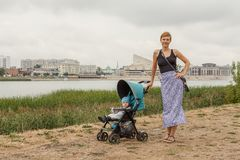 Caucasian woman walking in the park with her son in the baby carriage Stock Photos