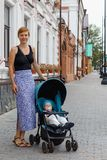 Caucasian woman walking in the park with her son in the baby carriage Royalty Free Stock Photography
