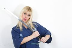 Caucasian woman wearing kimono and holding katana. Photo of blonde caucasian woman wearing kimono and holding katana Stock Photos