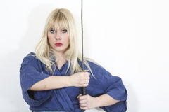 Caucasian woman wearing kimono and holding katana. Photo of blonde caucasian woman wearing kimono and holding katana Royalty Free Stock Photography