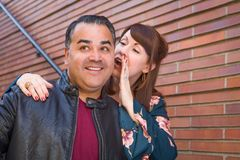 Caucasian Woman Whispering a Secret to Hispanic Man stock images