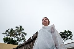 Caucasian woman in white plastic rain coat standing and looking ahead. Bad weather during vacation in Sri Lanka Royalty Free Stock Photography