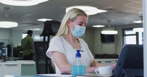 Woman wearing face mask using computer at office