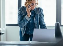 Businesswoman working on laptop and talking on mobile phone Stock Images