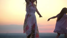 Caucasian woman with wreath on head with little daughter in summer dresses dancing on the hill at sunset stock video