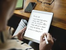Caucasian woman writing to do list on tablet Stock Image