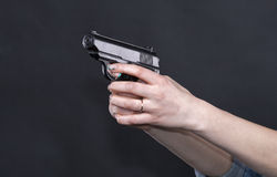 Caucasian women arms holding a gun against black background Stock Images