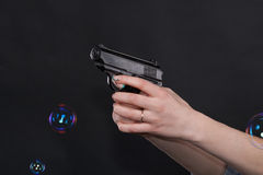 Caucasian women arms holding a gun against black background Stock Photography
