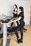 Exercising on treadmill. Caucasian women exercising on treadmill in gym. Female trainer manages electric muscle stimulation purposed to increase effectiveness of Royalty Free Stock Image