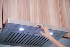 Caucasian women hand using the range hood in modern kitchen Royalty Free Stock Images