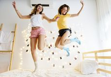 Caucasian women jumping on the bed together Stock Images