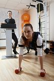 Push ups with EMS. Caucasian women makes push ups in gym. Female trainer standing aside manages electric muscle stimulation purposed to increase effectiveness of Royalty Free Stock Images