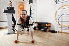 Push ups. Caucasian women makes push ups. Smiling female trainer standing aside manages electric muscle stimulation purposed to increase effectiveness of Royalty Free Stock Photo