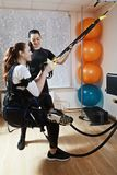 Exercise with tourniquet. Caucasian women wearing electric muscle stimulation suit makes exercise with tourniquet. Couch assists. Vertical shot Stock Photography