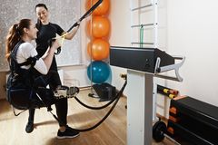 Training with tourniquet. Caucasian women wearing electric muscle stimulation suit training with gymnastic tourniquet. Smiling couch standing close and assists Stock Photography