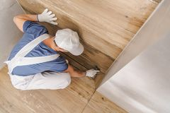 Grouting and Sealing Shower. Caucasian Worker Grouting and Sealing Shower Cabin Using Silicone and Grout. Bathroom Remodeling royalty free stock image