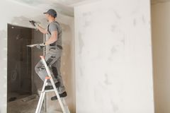 Worker Patching Drywall stock images