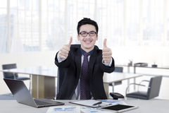 Caucasian worker shows thumbs up in office Stock Photography