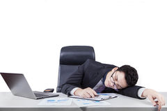 Caucasian worker sleeping on desk. Young entrepreneur looks tired and sleeping on desk with laptop and business documents Stock Photography