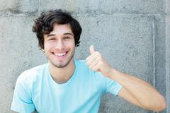 Caucasian young adult man with blue eyes showing thumb up. Outdoors with copy space Royalty Free Stock Images