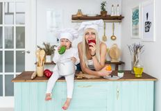 Caucasian young blonde mother and little beautiful daughter in white cook caps eat apple and mango on kitchen. Royalty Free Stock Photos