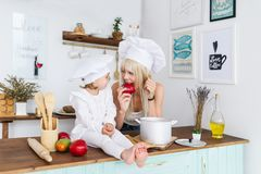 Caucasian young blonde mother and little beautiful daughter in white cook caps eat fruits on kitchen. Stock Image