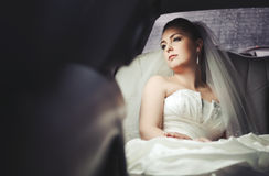Caucasian young bride sitting in limo. Stock Photography