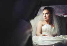 Caucasian young bride sitting in limo. Stock Photos