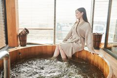 Brunette woman relaxing in jacuzzi in spa center with panoramic windows. Caucasian young brunette girl relaxing in jacuzzi in spa center, refreshing her body and royalty free stock photos