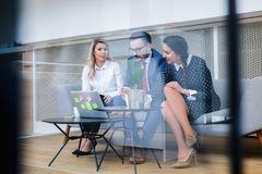 Caucasian business people meeting in boardroom behind glass royalty free stock photo