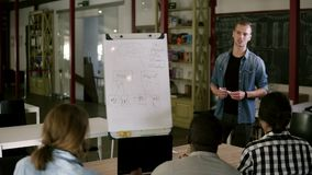 Caucasian young coach gives presentation for businesspeople working with flipchart, diverse multiracial team sitting in stock video footage