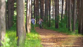 Caucasian young couple having fun enjoying cycling in forest stock footage
