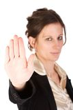 Caucasian young female motioning to stop. Brunette business woman holding hand up, looking annoyed. Hand in focus, face out of focus Stock Image