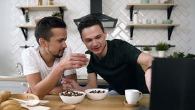 Caucasian young gay couple is sitting at the kitchen table eating breakfast and watching movie in the morning at kitchen. Lovely family gay couple concept stock video footage