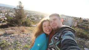 Caucasian young loving couple. Adventure Selfie. Caucasian young loving couple taking selfie while they walking on mountains near the sea stock video footage