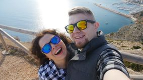 Happy young loving couple taking selfie on mountains near the sea. Caucasian young loving couple taking selfie on mountains near the sea stock footage