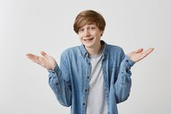 Caucasian young male has hesitant and excusing face expression, gestures doubtfully, has no answer on difficult question. Being puzzled or confused. Fair Royalty Free Stock Photography
