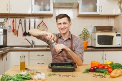 Handsome caucasian young man, sitting at table. Healthy lifestyle. Cooking at home. Prepare food. Caucasian young man in apron sitting at table with vegetables Royalty Free Stock Photo