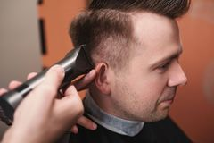 Caucasian young man in Barbershop. Barber is cuttinhg his hair in hipster style. Royalty Free Stock Images